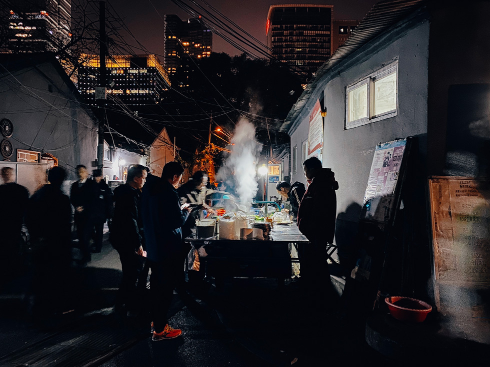 People on a dark street watching food being cooked.